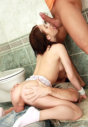 Naughty teenage brunette pleasing two cocks in the toilet