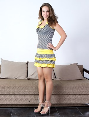 Hairy girl Alice L looks cute in her yellow striped skirt. She stands next to the couch and strips off her skirt and top. Then her bra and panties before playing with her hairy pussy.