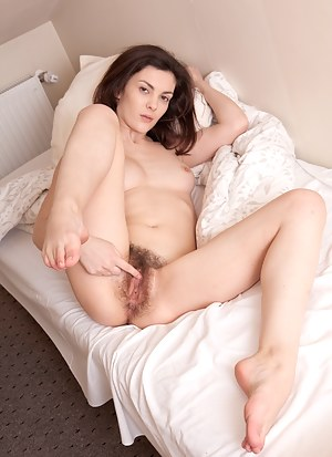 Natural beauty Karin gently rubs her hairy clit after she lifts her long legs in the air and lays in the sunlight.
