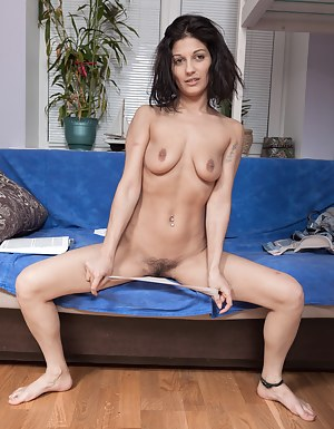 Kassiana is enjoying a book on her blue couch, and takes off her white blouse and denim jeans to unwind. She has beautiful natural breasts and a hairy bush that she fingers and masturbates with today.