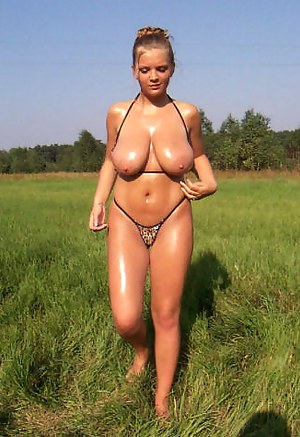 Chubby girl has her astounding natural tits oiled and is fingering her juicy twat in the middle of a field wearing her hot bikini.