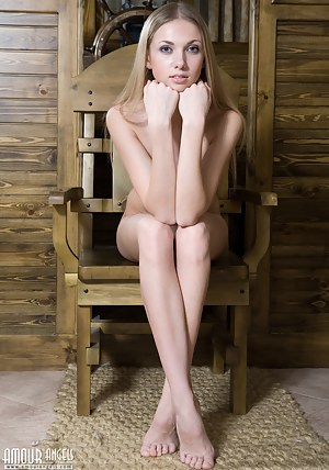 Longhaired blonde girl poses in the altogether on the chair for you.
