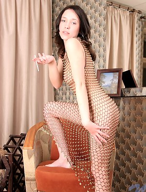 Teen in fishnet outfit smoking while posing sexy indoors