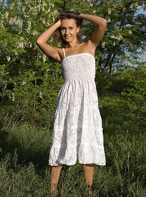 Enchanting teen with an innocent look taking off white dress and posing naked in the nature.