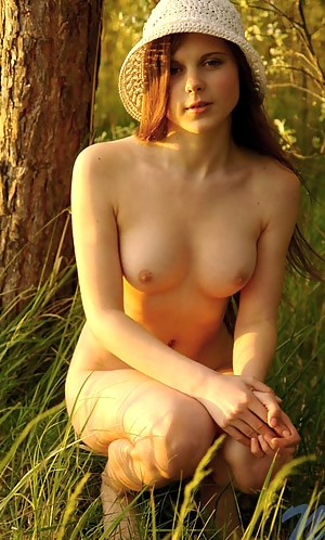 Charming honey girl with tasty body goes totally naked on a tree trunk