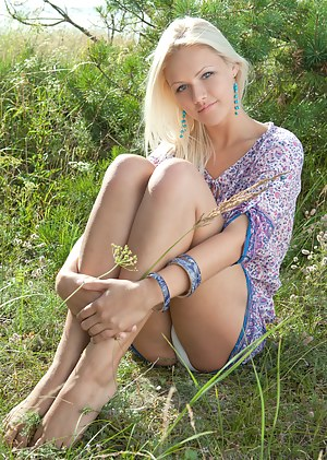 Remarkable blonde teen model stripping clothes and spreading legs outdoor on the nature.